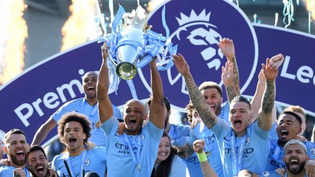 A LEAGUE APART: Kompany holds the Premier League trophy aloft after City's successful 2018/19 title defence