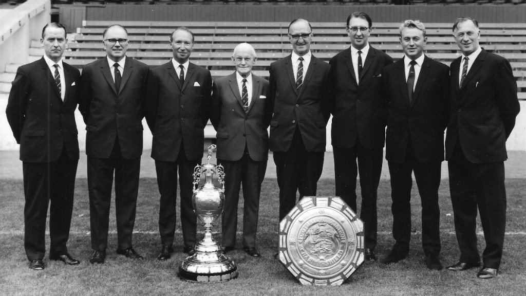 ALL SMILES: Joe (far right) proudly poses with the City directors - along with the Division One trophy and Charity Shield