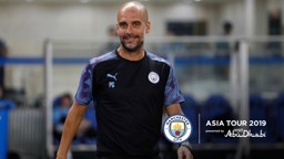 ALL SMILES: Pep Guardiola heads out to training in China.