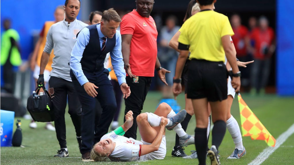 WORRY: Concerned England boss Phil Neville rushes over to Steph Houghton after the injury to the Lionesses skipper