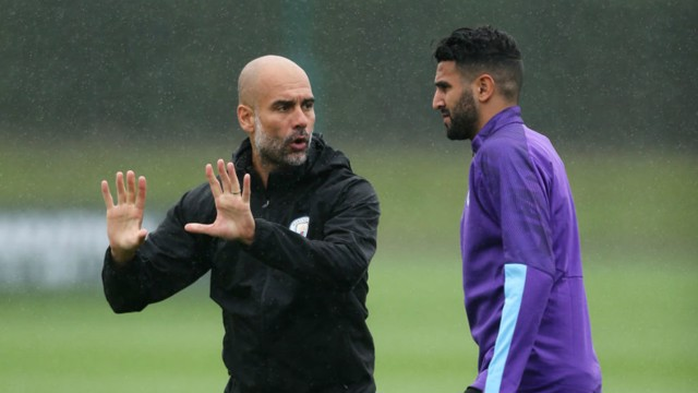 TALKING TACTICS: Pep Guardiola speaks to Riyad Mahrez on the training pitch.