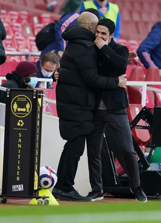REUNITED : Guardiola and Artera share a warm embrace on the touchline.