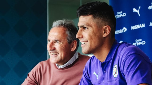 ALL SMILES : Rodri can't contain his happiness as he puts pen to paper and signs his City contract alongside Txiki Begiristain