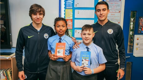 READ ALL ABOUT IT: Adrian Bernabe and Eric Garcia celebrate World Book Day with two youngsters from Mount Carmel RC Primary School