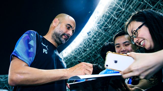 THE BOSS : Pep Guardiola makes these supporters' night complete!