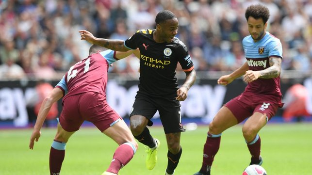 QUICK FEET : Raheem Sterling skips past a pair of challenges.