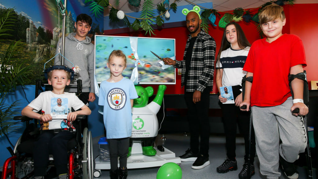 ALL TOGETHER NOW : Fabian Delph with some of the young Royal Manchester Children's Hospital patients during the unveiling of the 3D pain distraction unit