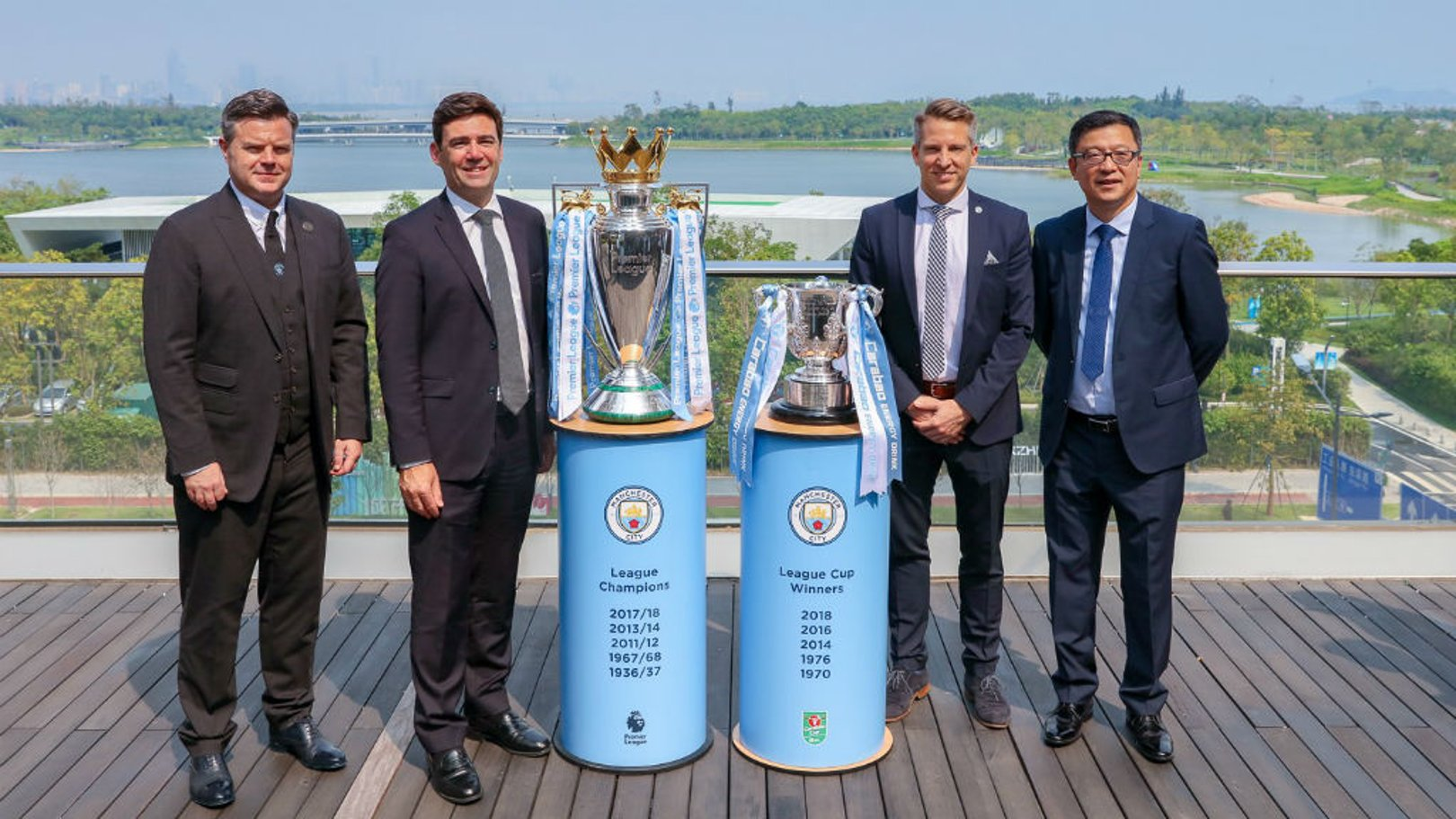 ndy Burnham, Mayor of Greater Manchester (second left) is pictured in Shenzhen with City Football Group executives and the Premier League and Carabao Cup trophies that were won by Manchester City last season.