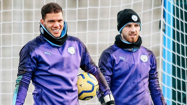 TWO'S COMPANY : Ederson and Daniel Grimshaw were wrapped up to keep out the winter chill