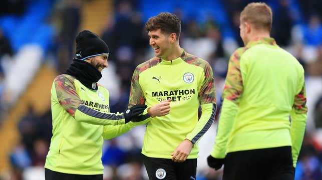ALL SMILES : Aguero and Stones share a joke during the warm up.