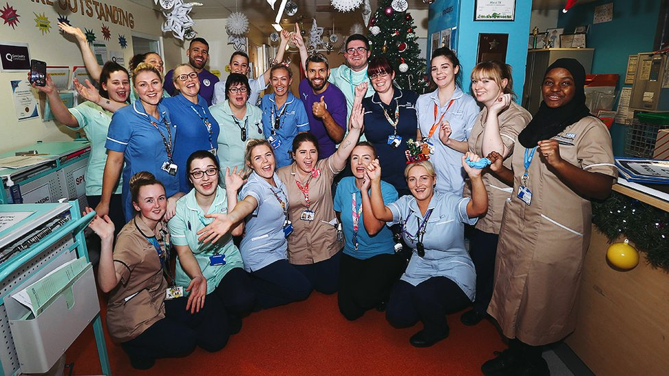 FESTIVE CHEER : Nicolas Otamendi and Sergio Aguero spend some time with staff and volunteers
