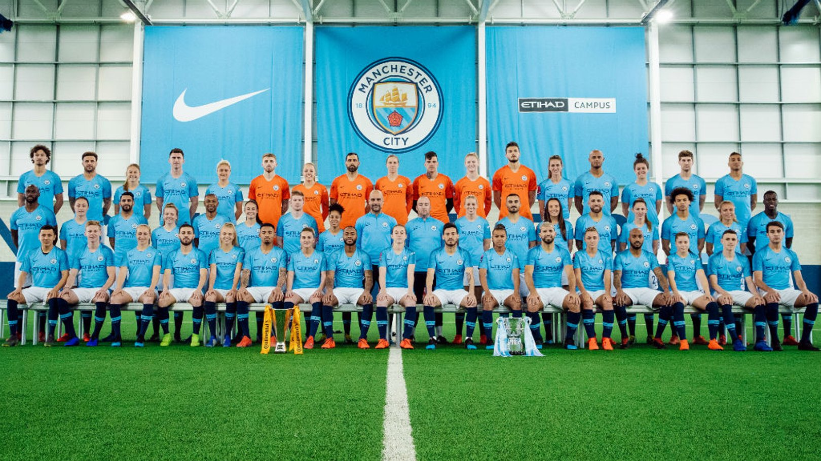 HISTORY MAKERS: Pep Guardiola and Nick Cushing line up alongside their two squads with the Continental and Carabao Cups proudly on display