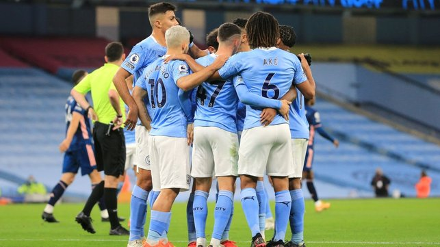 GROUP HUG : The players gather to celebrate Sterling's opener in the 23rd minute.