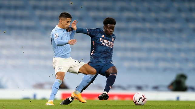 BATTLING JOAO : Cancelo fights Saka for the ball in the first half.