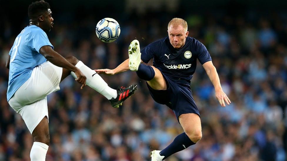 AERIAL BATTLE : Kolo Toure leaps alongside Paul Scholes to win possession