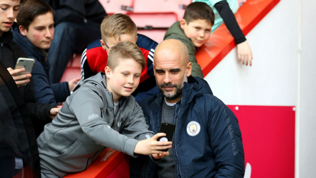 CENTRE OF ATTENTION : The boss poses for a picture with some happy young Bournemouth fans prior to kick-off